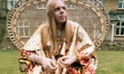 Rick Wakeman of Yes sits on a wicker chair wearing a glittering gold lame bathrobe
