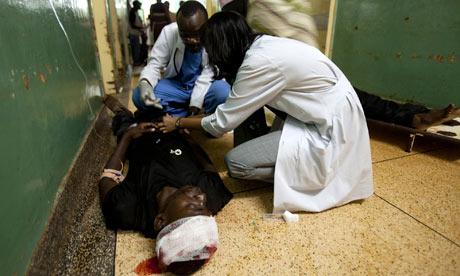 Paramedics attend a victim of the Kampala bomb