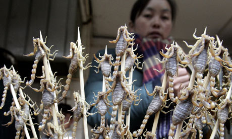 A Chinese woman selling scorpions on stick