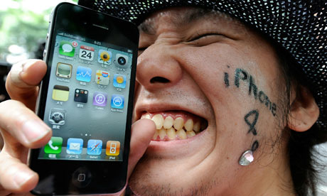 A man holds his iPhone 4 in front of a m
