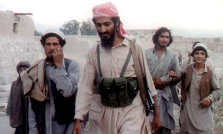 Bin Laden center walks with. Osama Bin Laden walks with