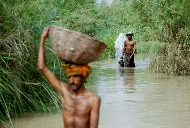 A family wades through flood waters in Shah Bela, Pakistan