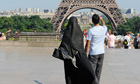 A woman wearing niqab walks at Square Trocadero near the Eiffel Tower in Paris