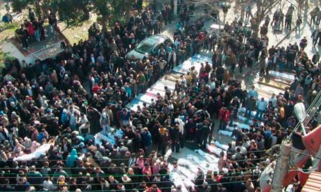 Residents at a funeral said to be for the victims of the Homs attack. Photograph: Reuters