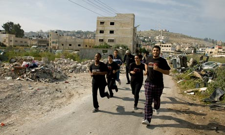 drama students run through Jenin refugee camp
