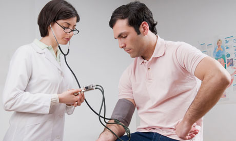 Female doctor checking man's blood pressure