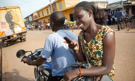 Ugandan woman texts on motorcycle taxi