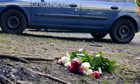 A bouquet of roses is seen on the place where four people were shot dead in the French Alps