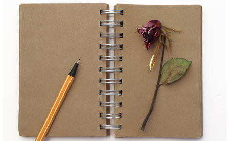 old style notebook and dead red rose