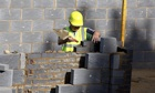 A worker lays bricks at a building site