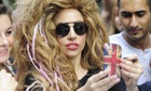 Lady Gaga in a wig holding up a mobile phone to take a picture