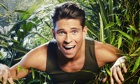 A grinning Joey Essex, from I'm A Celebrity, with a jungle plant