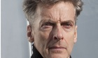 Peter Capaldi in a high-collar jumper, squinting in the sun