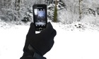 Gloved hand taking picture of snow with mobile phone camera