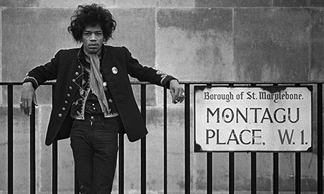 Jimi Hendrix, looking serious, leaning against railings at Montagu Place, London