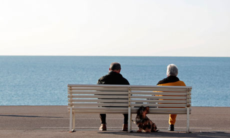 Elderly people sit on a bench by the seaside