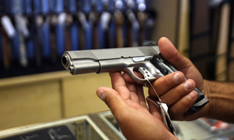 A man chooses a gun at the Gun Gallery i