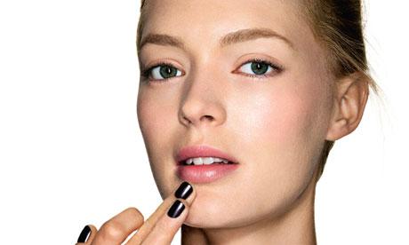 A woman applying face cream