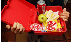 A child's hands holding a lunchbox with a Coke, sandwich, apple, KitKat