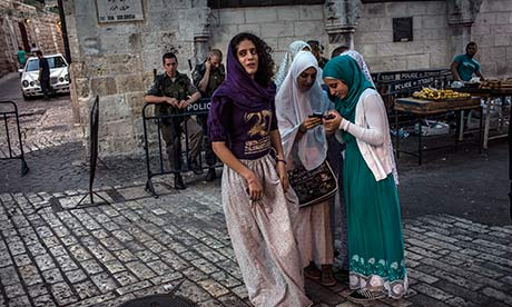 Arab women watched by Israeli soldiers in Jerusalem