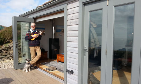 Stan Cullimore and his dog in the doorway of his luxury shed
