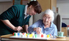 Elderly woman patient plays solitaire with a nurse