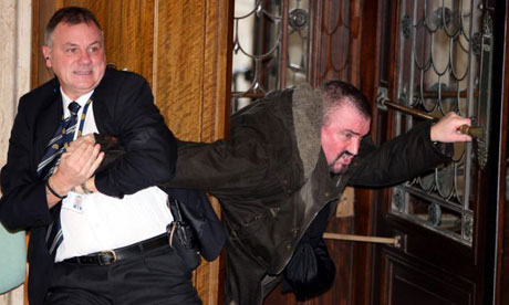 Michael Stone is restrained by security staff at the front doors of the Stormont parliament building in Belfast, in November 2006. Photograph: Paul Faith/PA Wire