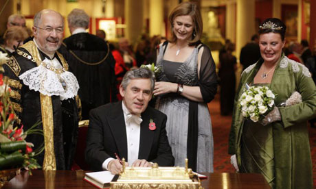 The lord mayor of London, Ian Luder, and his wife, Lin (far right), watch as Gordon Brown signs the distinguished visitors' book, while his wife Sarah stands behind him, in the Guildhall in London on November 10 2008. Photograph: Shaun Curry/PA Wire