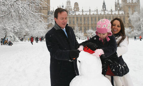 David Cameron and Carol Vorderman help a child build a snowman near the Houses of Parliament