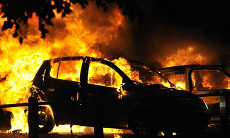 Cars burn on a street in Ealing, as riots spread across London and beyond