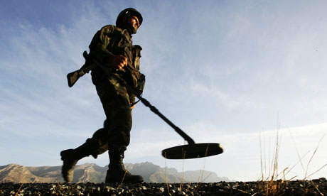 A soldier patrols with a landmine detector