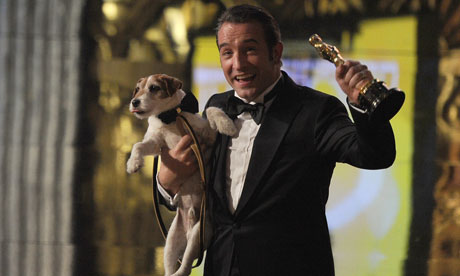 Best actor winner Jean Dujardin walks off the stage with dog Uggie