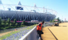 A security worker stands near the Olympic Stadium in London