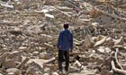 A man stands on the debris of destroyed buildings after an earthquake in north-west Iran