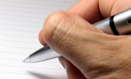 A hand holding a pen above a blank page of a spiral notebook.