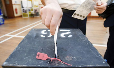 Voter placing card into ballot box