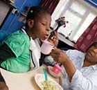 Mother assisting disabled daughter with feeding