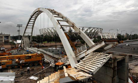 Indian workers stand at the scene of bridge collapse near Jawaharlal Nehru stadium in New Delhi