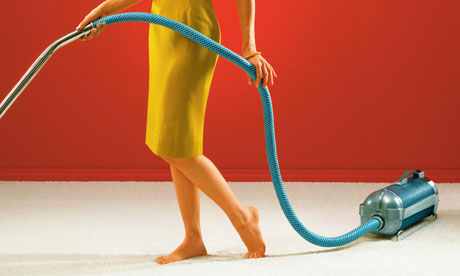 Woman cleaning carpet with vintage vacuum cleaner