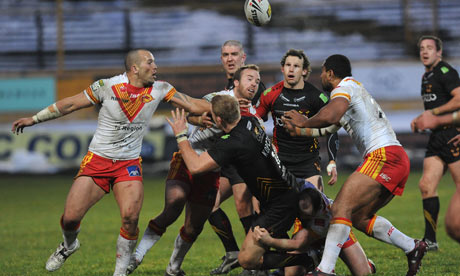 Bradford Bulls' Craig Kopczak releases the ball as he is tackled by Ben Fisher of Catalan Dragons