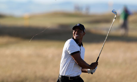 Tiger Woods plays a shot out of the rough on the 18th during the first