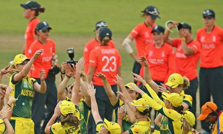 The dejected England women's cricket team look on as Australia celebrate their World Twenty20 win