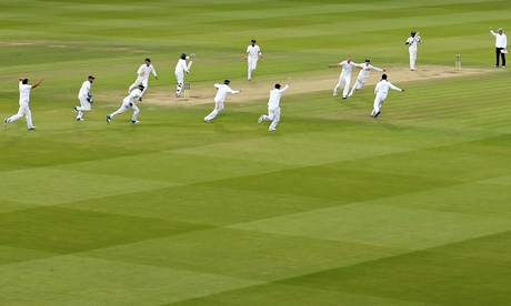 England's players celebrate after Sri Lanka's last man, Nuwan Pradeep, is given out – only for the d