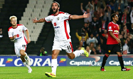 White riot … Will Grigg of MK Dons celebrates scoring against Manchester United in the Capital One C
