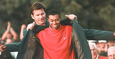 Tiger Woods is presented with his winner's jacket by Nick Faldo