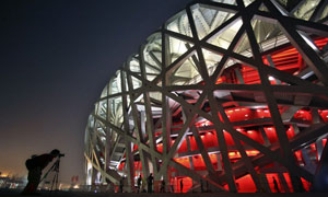 A photographer focuses on the National Stadium, also known as the Bird's Nest, in Beijing