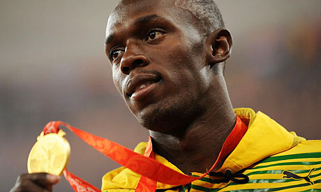 Usain Bolt showing one of his golden olympic medals.
