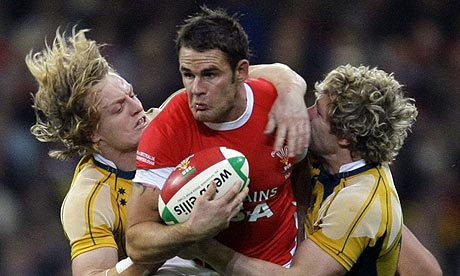 Wales' Lee Byrne is tackled by Australia's Ryan Cross and Peter Hynes