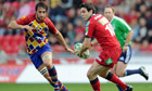 Scarlets's Stephen Jones, right, prepares to pass under pressure from Perpignan's Bertrand Guiry.