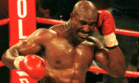 Evander Holyfield winces after Mike Tyson bites his ear.